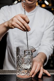 バースプーンでカクテルグラスで飲み物をかき混ぜるバーでカクテルを事前に準備するバーテンダー