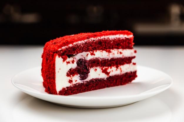 白いプレート上のチェリーと赤いベルベットケーキ