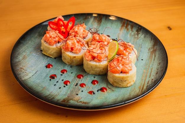 青い皿に上に魚と新鮮なマキ