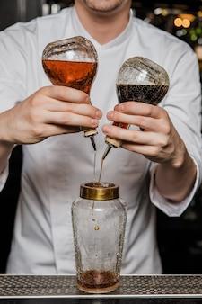 Бармен готовит коктейль в баре, добавляя битер в шейкер