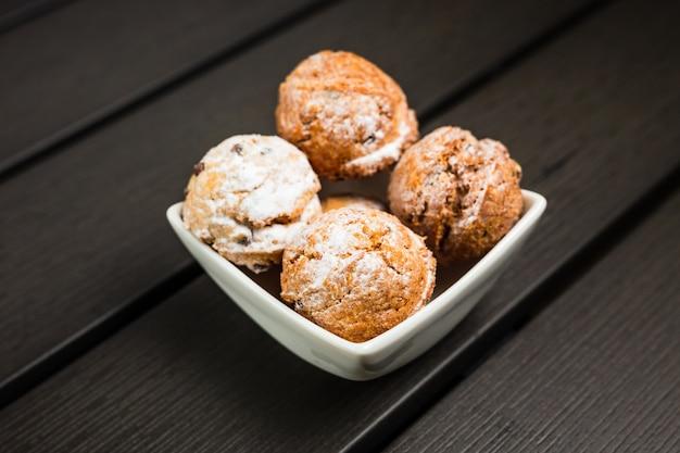 白いボウルに粉砂糖で覆われた小さな丸いクッキー