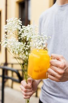 レモネードと花の瓶を握る男