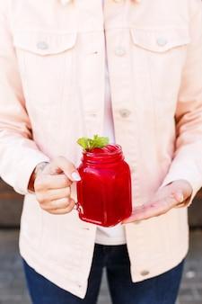 瓶の中のさわやかなイチゴとミントレモネードを彼女の手で保持しているピンクの女性