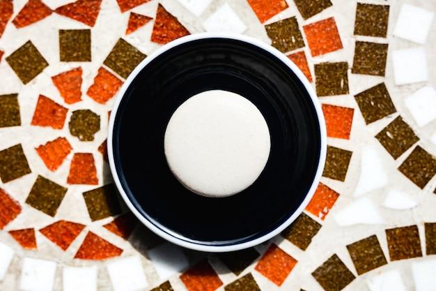Ванильное макарон на темной тарелке на мозаичном каменном столе, вид сверху