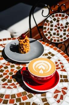 晴れた日にカフェテラスのモザイクの石のテーブルでカプチーノコーヒーとデザートの作りたての赤いカップ