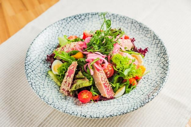 Салат из филе тунца с листьями салата и овощами