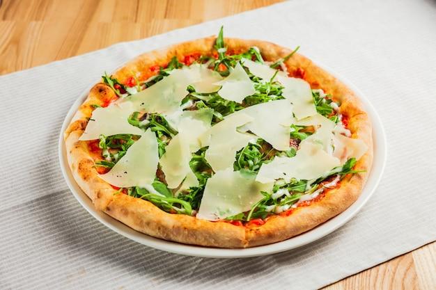 白いプレートにルッコラまたはロケットとパルメザンチーズのピザ