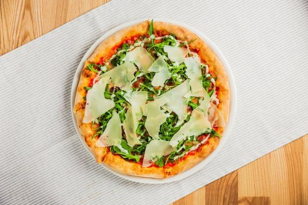 白いプレート、上面にルッコラまたはロケットとパルメザンチーズのピザ