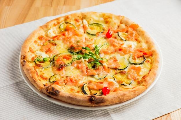 ズッキーニ、赤い魚とチーズ、白い皿の上のピザ