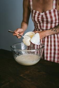 赤と白のチェックドレスの若い女性がケーキを焼く、大きなガラスにサワークリームを追加