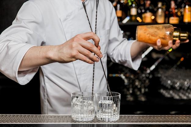 Бармен охлаждает бокалы и одновременно встряхивает коктейль