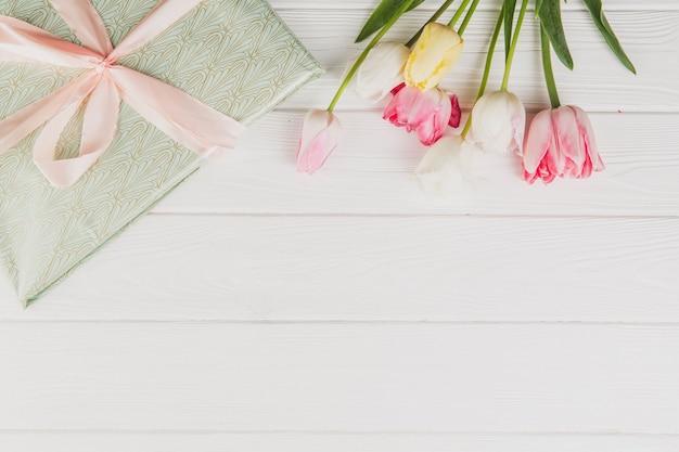 幸せな女性の日。チューリップの花束と白い木製の背景のギフトボックス。