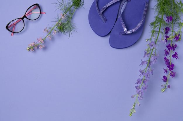 紫のボード上のビーチサンダル、サングラス、花