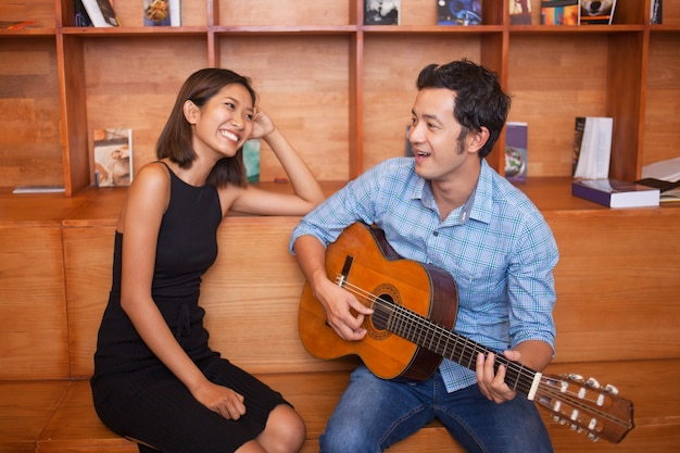 男が歌うと女の笑顔のためにギターを演奏します