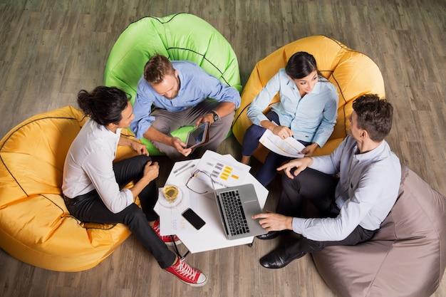Люди и обсуждать идеи сидя в кафе таблице