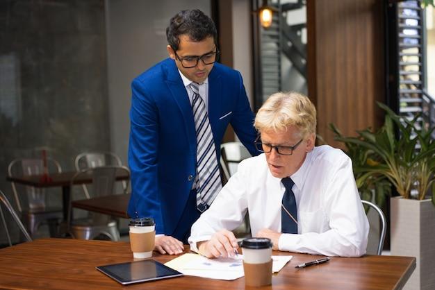オフィスカフェでのレポートを確認している同僚