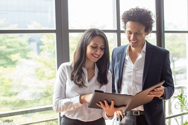 Счастливые деловые партнеры, читающие условия договора