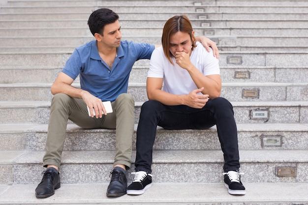 屋外の階段に怒っている友を結んでいる男