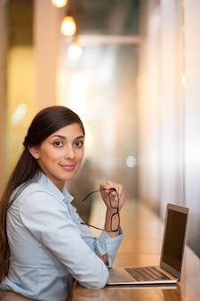Улыбаясь бизнесмен работает на ноутбуке в кафе