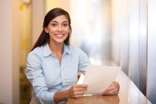 Улыбается довольно женщина, держащая документ в кафе