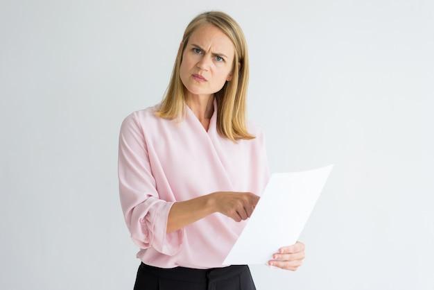 報告書に不満を持ち、紙に間違いを指している不満を抱いた女性の上司。