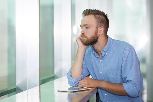 Усталый менеджер, глядя в окно офиса