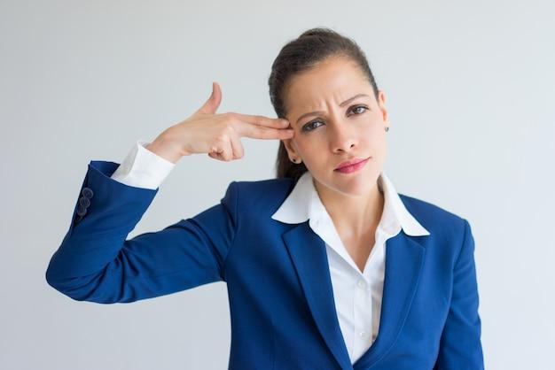 Скучно бизнес-женщина показывает выстрел выстрел и самоубийственный жест.