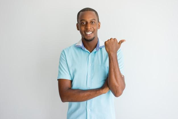 喜んで成功したアフリカの男を指差し、カメラを見て。