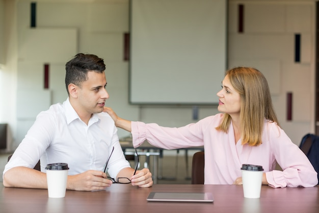 コーヒーブレイクで肩に男性の同僚をタップしている自信のあるビジネスマン。
