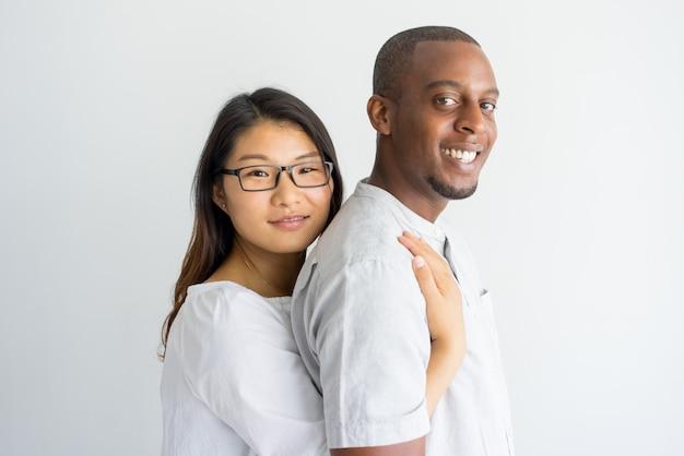 カメラを見て幸せな興奮した若い多民族のカップル。