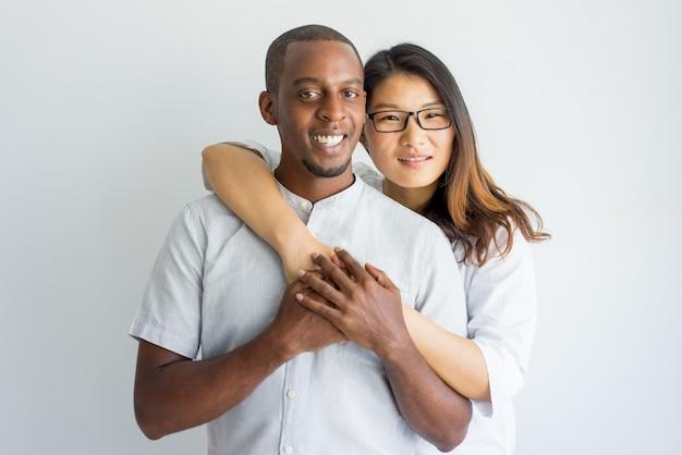 抱きしめるとカメラを見ている幸せな異人種カップル。