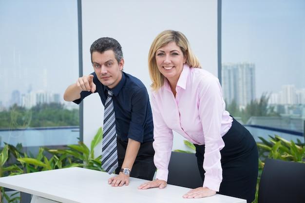 Положительные предпринимательные деловые люди, опираясь на стол и глядя на камеру