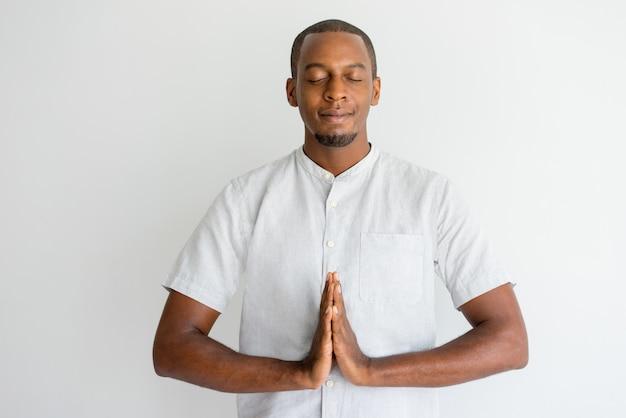 瞑想中にナレッジに手を触れている穏やかなアフリカの男。
