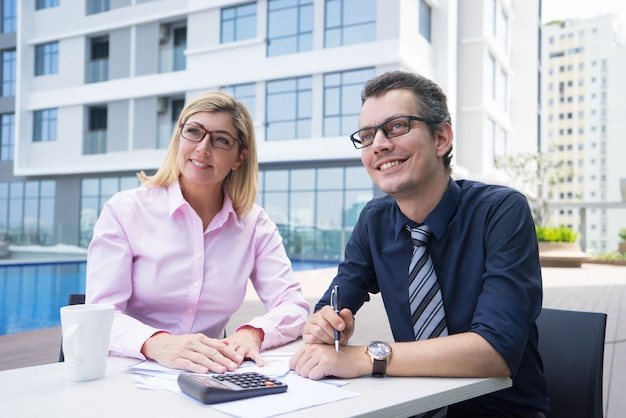 Улыбающиеся амбициозные бухгалтеры, сидящие за столом с бумагами и калькулятором