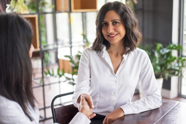 カフェでパートナーと握手をしている笑顔のビジネス女性。