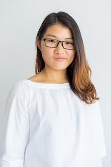カメラを見ている眼鏡で若い中国人女性をなだめさせる。