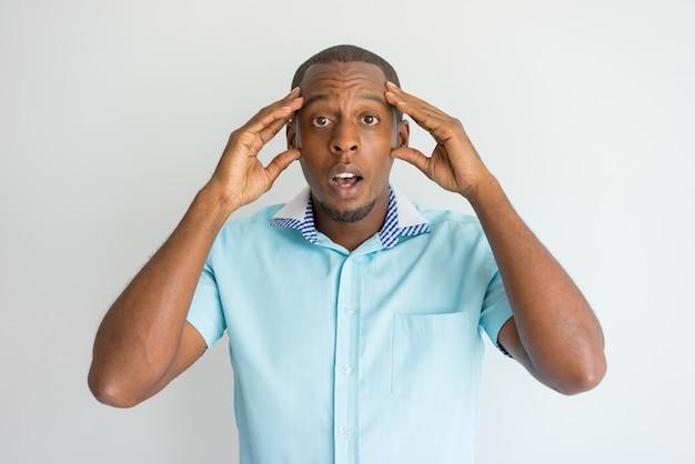 頭を痛めてカメラを見ている人に頭を痛めた衝撃的な男。