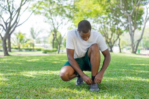 黒のスポーツマンは朝の運動を公園で準備しています。