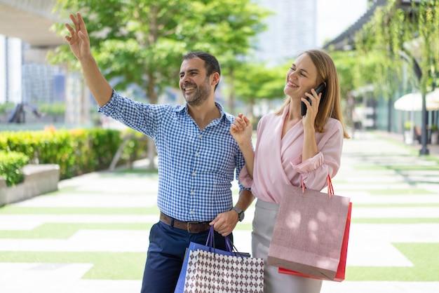 ストリートで誰かを挨拶する買い物客の優しいスタイリッシュなカップル。