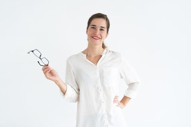 眼鏡を持ってカメラを見て、リラックスした若いかわいい女性。