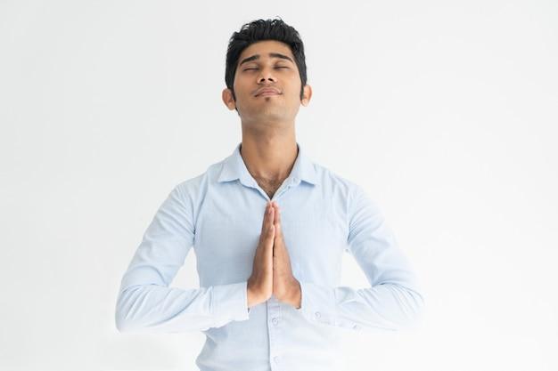 閉じた目で祈る白いシャツの穏やかなインド人。