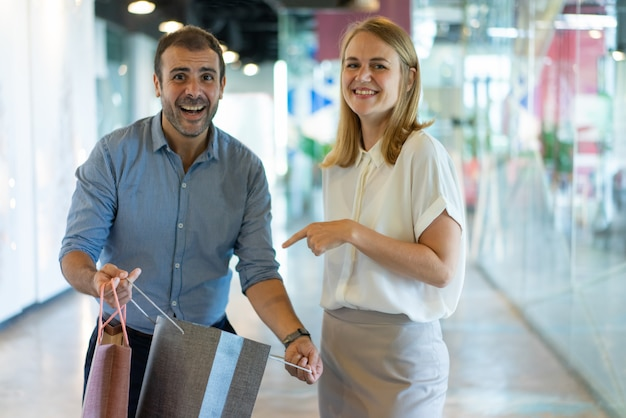 Улыбается женщина, указывая на покупку в бумажный мешок, проведенный муж в торговом центре