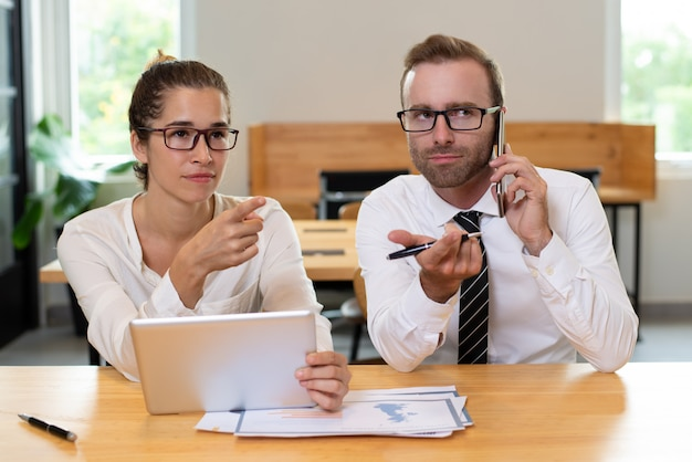 何かを指差し、デバイスを使用するビジネス同僚。