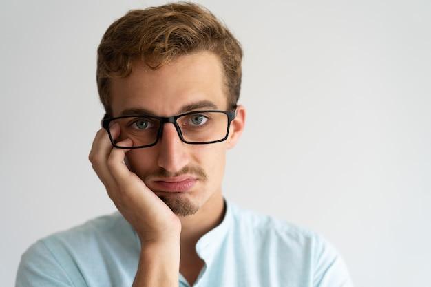 Макрофотография расстроен раздраженный блондин парень с отвращением лицо.