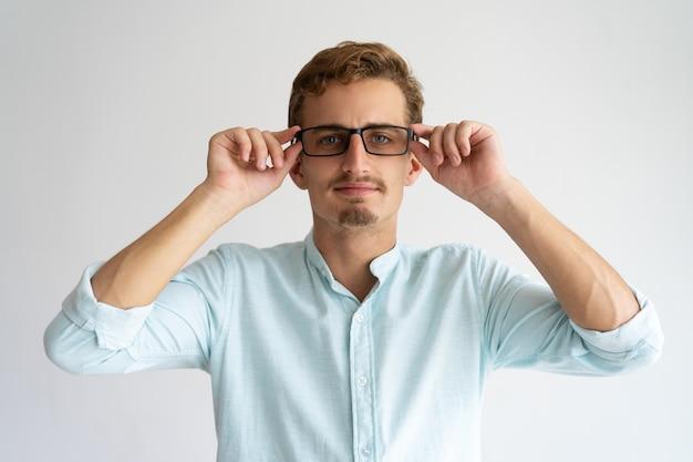 白いカジュアルなシャツでフレンドリーな陽気な男が眼鏡を調整。