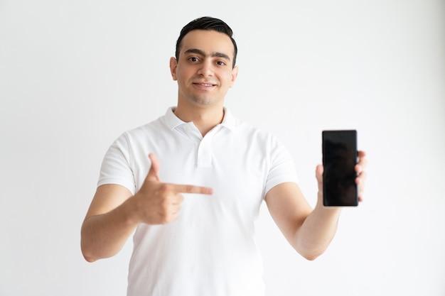 Улыбается молодой человек, указывая на смартфон и глядя на камеру.