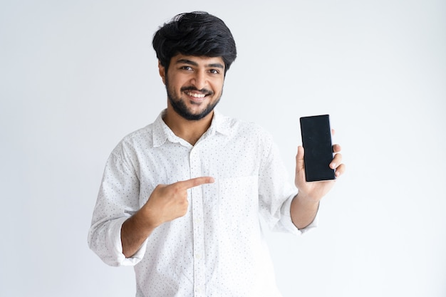 Улыбающийся молодой человек, указывая на смартфон и глядя на камеру