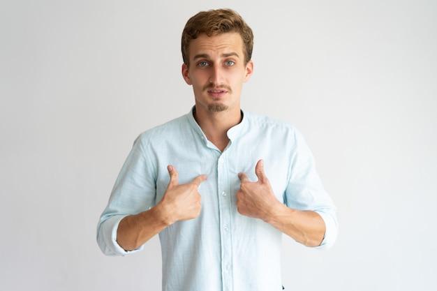 Удивленный и сомнительный парень в белой повседневной рубашке спрашивает, кто, я.