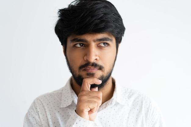 思いやりのある若い男が顎に触れて離れて見る。インドの男の考え。