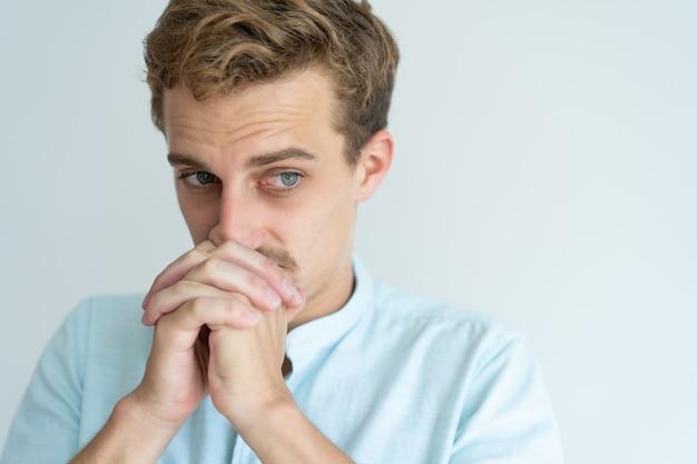 Задумчивый молодой человек, касаясь рот сжатыми руками и глядя в сторону.